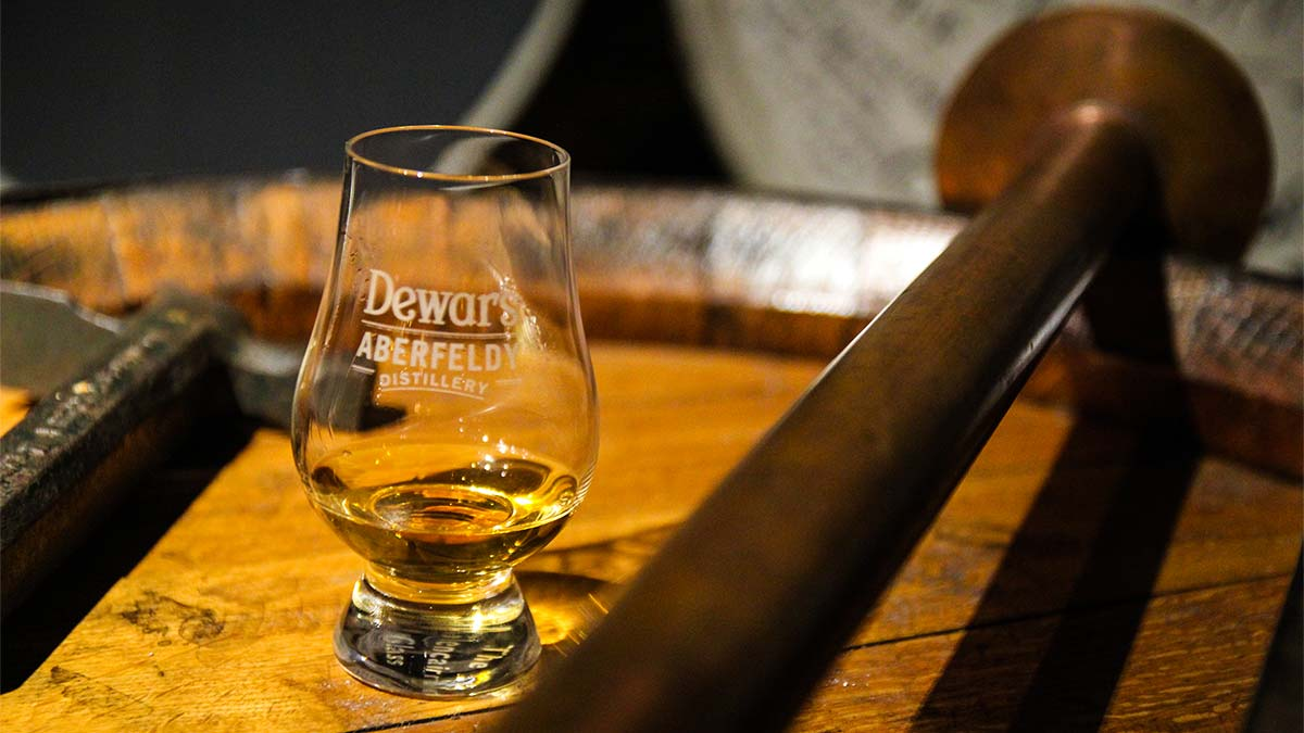 Nosingglas gefüllt mit Whisky auf Whiskyfass